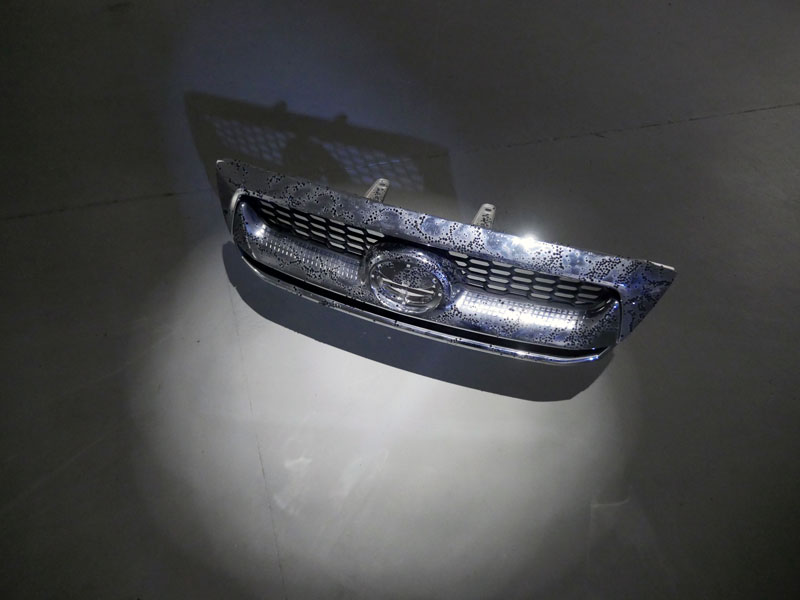 'A mysterious hum on the horizon (Night Stalker)', 2013<br>New car bumper bar, black plastic diamantes, disco ball motor, nylon thread<br>120 x 20 x 15 cm (ceiling suspended)