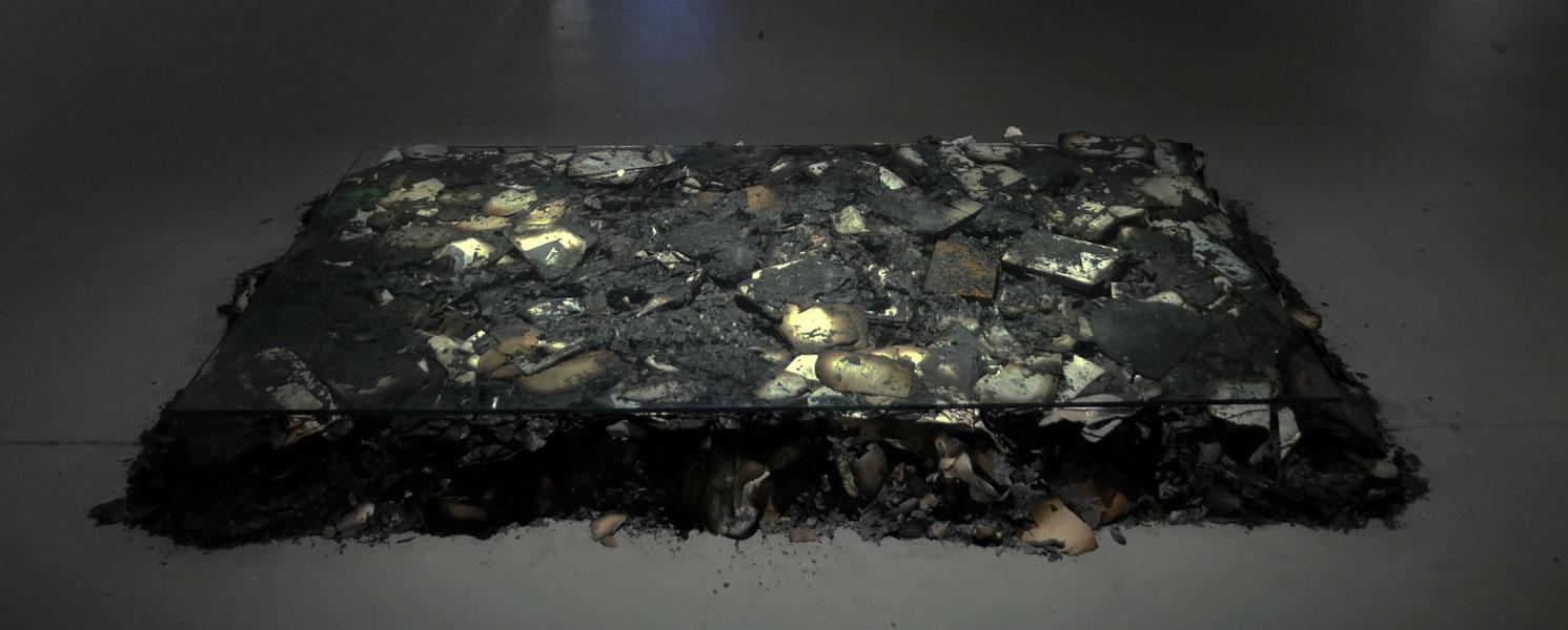 '†uff Drag Cul†', 2013<br>Burnt Art history books, a concerned stranger, shatter proof glass<br>120 x 100 x 15 cm