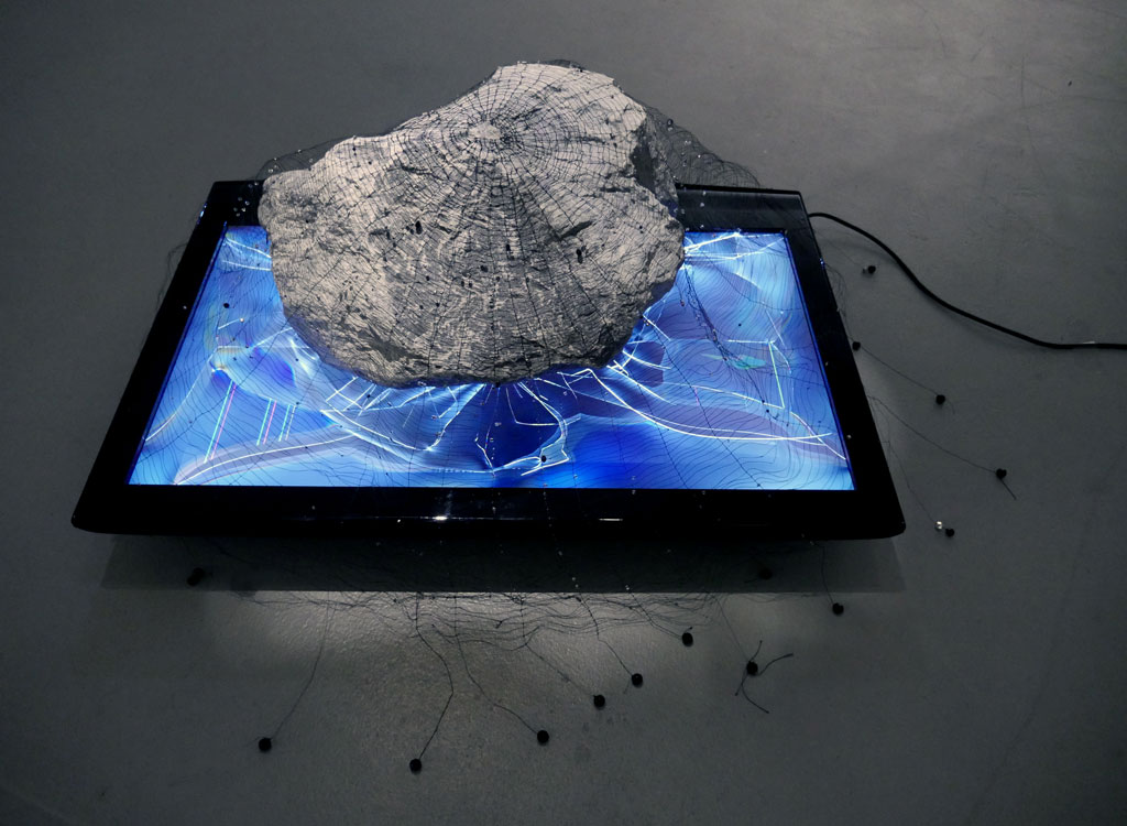 'determined obsolescence (forever young)', 2015<br>LCD TV, rock, linen upholstery thread and glass beads<br>120 x 80 x 60 cm